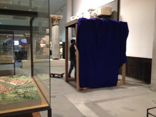 """cabine du jeu """"Antique en Kit"""" en cours d'installation à côté de la maquette d'Arles"""
